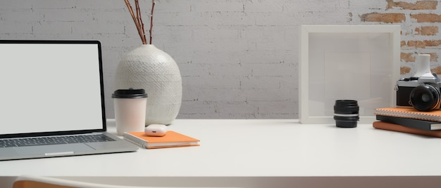 Vista ravvicinata dell'area di lavoro con mock up laptop, notebook, decorazioni e copia spazio sulla scrivania bianca