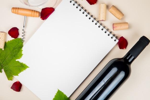 Vista ravvicinata della bottiglia di vino rosso e cavatappi con tappi di sughero su sfondo bianco decorato con foglie e petali di fiori con spazio di copia