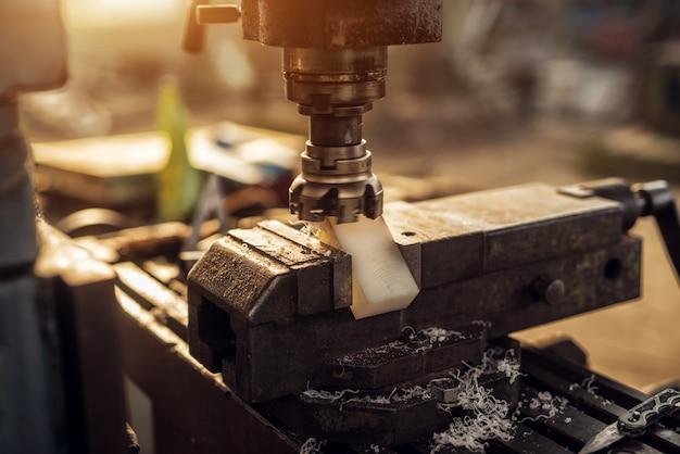 Vista ravvicinata della macchina rettifica parte in plastica sullo strumento morsa nell'officina industriale.