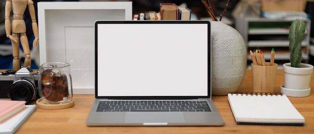Vista ravvicinata della scrivania da casa con laptop, cancelleria, tazza di caffè, forniture e decorazioni, tracciato di ritaglio.
