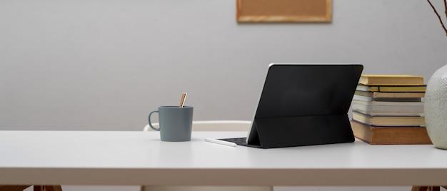 Vista ravvicinata della scrivania da casa con tavoletta digitale e libri