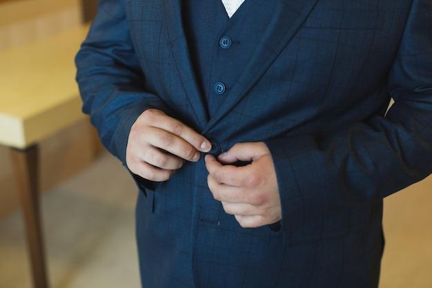Vista ravvicinata delle mani dello sposo che abbottona la giacca da sposa