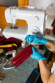 Vista ravvicinata delle mani di una donna che cuce una maschera