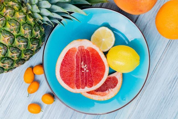 Vista ravvicinata di agrumi come pompelmo e limone nel piatto con kumquat di mandarino arancio ananas su fondo in legno
