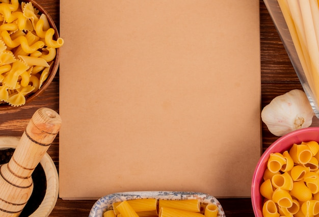 Vista ravvicinata di diversi tipi di maccheroni in ciotole con pepe nero e aglio con blocco note su superficie di legno con spazio di copia