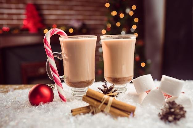 Vista ravvicinata di immagine composita di cioccolatini caldi contro l'albero di natale