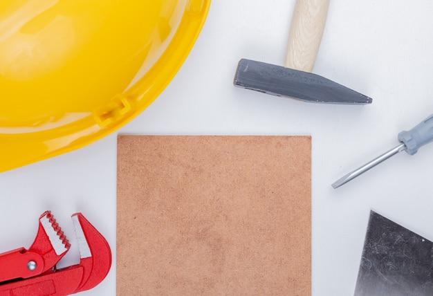 Vista ravvicinata di strumenti di costruzione come mattone martello casco di sicurezza cacciavite chiave a tubo coltello stucco intorno a piastrelle mettlach su sfondo bianco