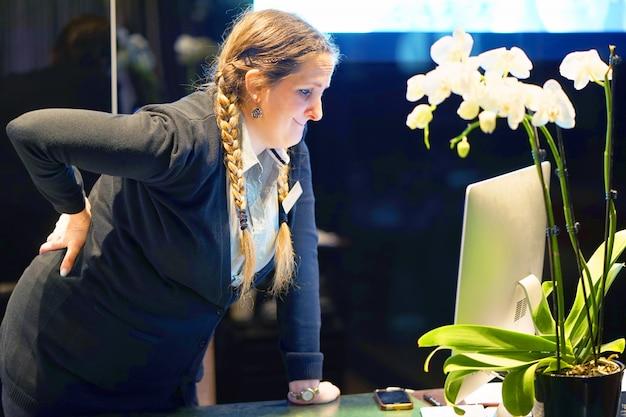 Vista ravvicinata di un manager dell'hotel donna-reception lavoratore con dolore ai reni. mal di schiena.