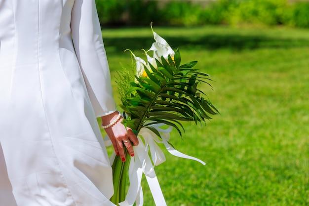 Vista ravvicinata di una sposa in possesso di un mazzo di fiori bianchi