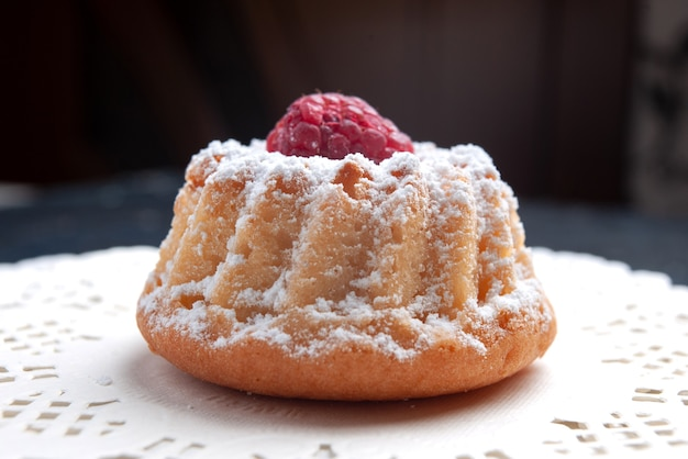 Vista ravvicinata frontale deliziosa torta con panna e lampone rosso sullo zucchero del biscotto di frutta torta superficie scura