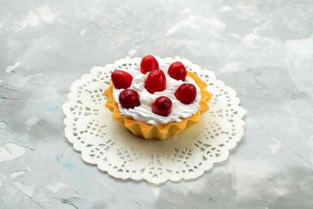 Vista ravvicinata frontale piccola deliziosa torta con crema e frutti rossi sul tè dolce superficie leggera