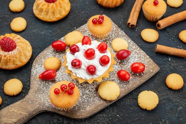 Vista ravvicinata frontale piccole torte gustose con crema di cannella e frutta fresca sulla bacca di frutta dessert torta biscotto dolce scrivania scuro