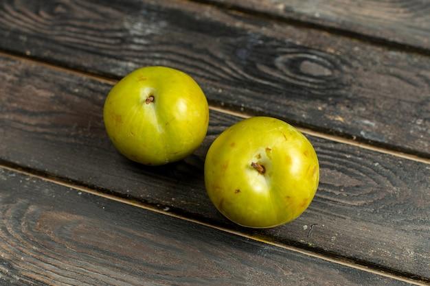 Vista ravvicinata frontale verde ciliegia-prugne frutta mellow e aspro sulla vitamina di frutta sfondo marrone