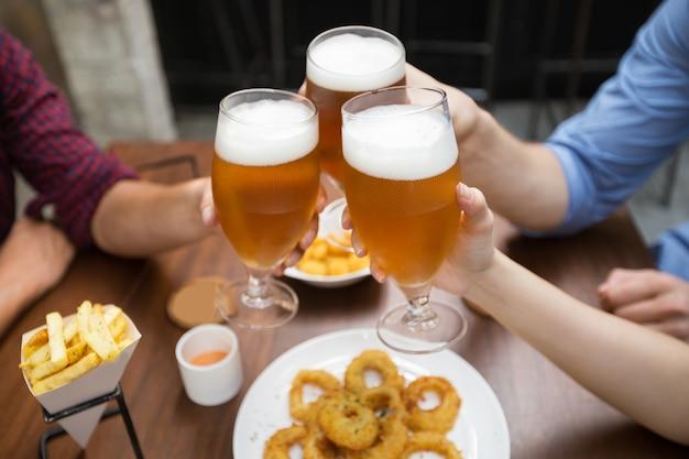 Vista ritagliata degli amici clinking glasses of beer