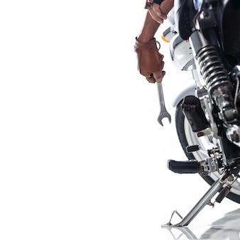 Vista ritagliata del meccanico che utilizza una chiave su un motociclo su fondo bianco