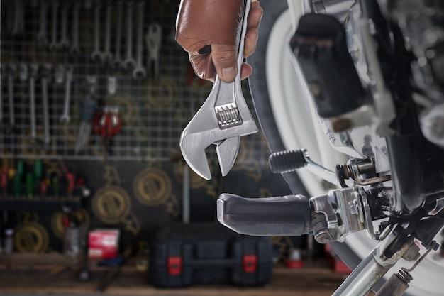 Vista ritagliata del meccanico usando una chiave su una moto