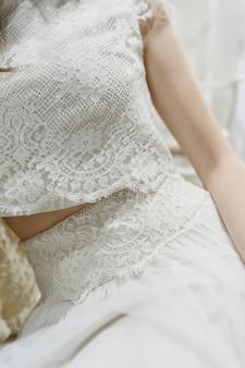 Vista ritagliata della sposa in abito di pizzo nel salone di nozze