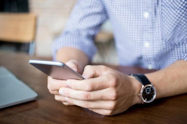 Vista ritagliata di uomo che tenta su smartphone