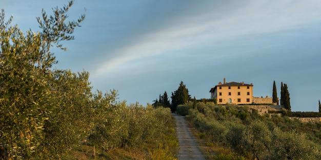 Vista scenica della strada non asfaltata e della casa in villaggio, toscana, italia