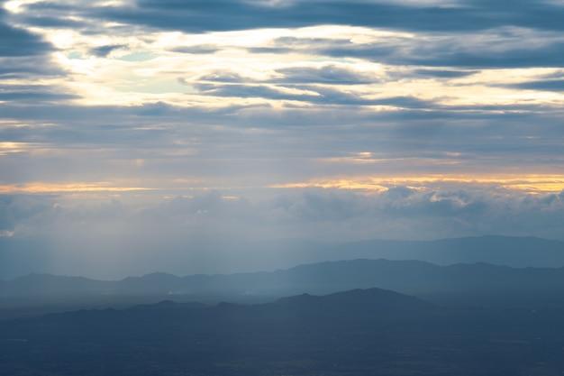 Vista scenica delle montagne della siluetta contro il cielo durante il tramonto e il fascio