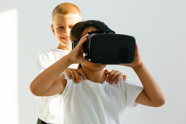Vista selettiva di due bambini piccoli che utilizzano cuffie per realtà virtuale