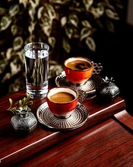 Vista sie di una tazza di cioccolato servito con un bicchiere d'acqua sul tavolo