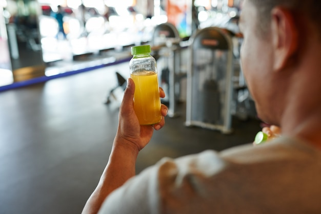 Vista sopra la spalla di un uomo irriconoscibile in possesso di una bottiglia di succo d'arancia