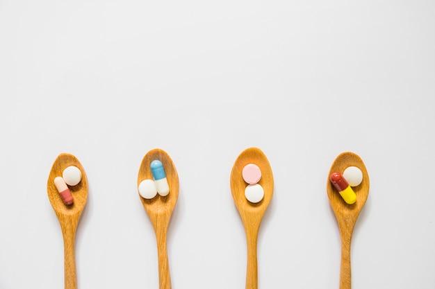 Vista sopraelevata dei cucchiai di legno con le pillole isolate su fondo bianco