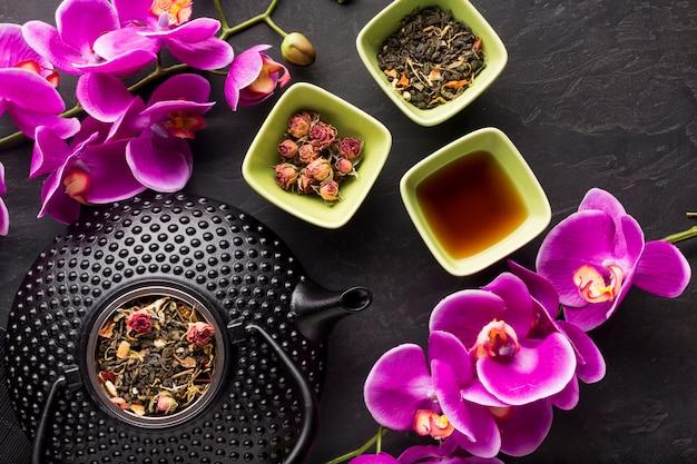 Vista sopraelevata del fiore rosa dell'orchidea e dell'erba del tè sul contesto nero
