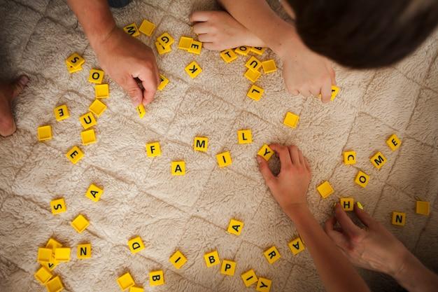 Vista sopraelevata della mano che tiene le lettere del gioco di scrabble sul tappeto della coperta