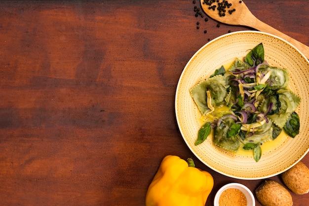 Vista sopraelevata della pasta verde dei ravioli con peperone dolce e pane gialli su superficie di legno