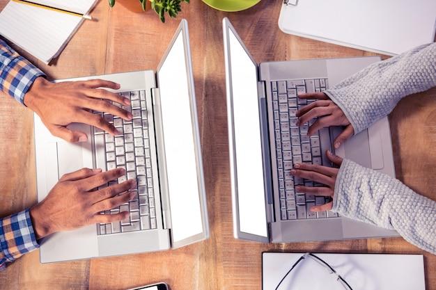 Vista sopraelevata delle mani che digitano sulla tastiera del computer portatile allo scrittorio in ufficio creativo