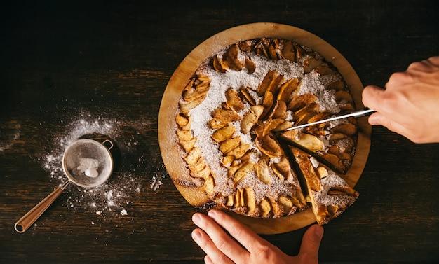 Vista sopraelevata delle mani maschii che tagliano la torta di mele al forno domestica sul fondo di legno scuro rustico della tavola