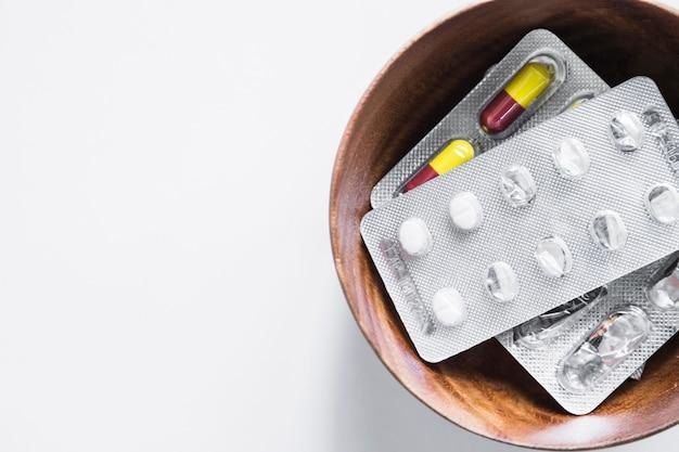 Vista sopraelevata delle pillole del blister in ciotola su fondo bianco