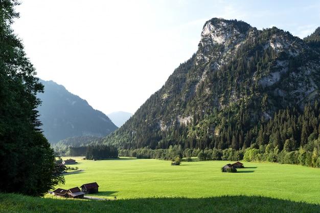 Vista sui prati alpini ben curati con annessi sullo sfondo delle montagne.