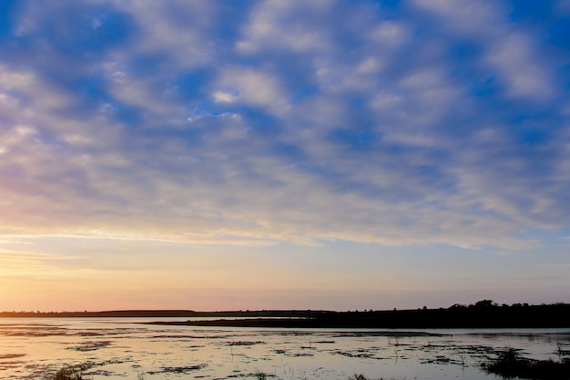 Vista sul fiume di sera, nuvole di altocumulus.