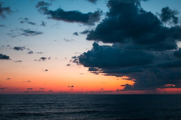 Vista sul mare al tramonto con cielo drammatico e nuvole colorate