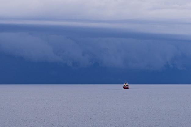 Vista sul mare con grandi nuvole di temporale sopra la superficie del mare con rimorchiatore