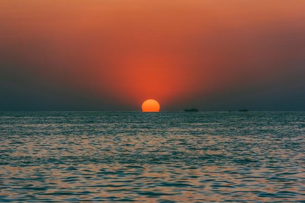 Vista sul mare con il sole al tramonto e le navi