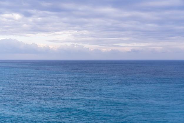 Vista sul mare con l'orizzonte del mare e cielo blu profondo quasi chiaro, fondo, spazio della copia
