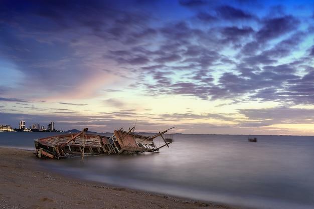 Vista sul mare con la barca del naufragio nell'oceano a tempo la mattina