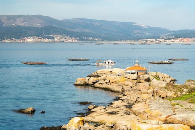 Vista sul mare con la navigazione della barca del mitilo e del faro