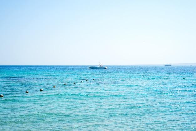 Vista sul mare con pietra costa e barche parcheggiate.