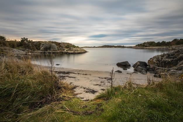 Vista sul mare con rocce, mare e nuvole. grimstad in norvegia