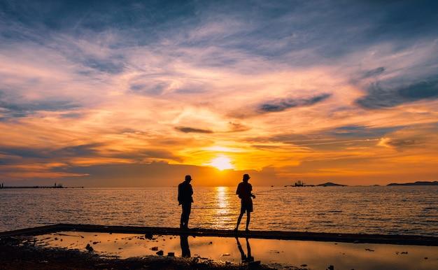 Vista sul mare crepuscolare il tramonto e l'oro chiaro con la priorità alta della siluetta del pescatore sull'isola in tailandia