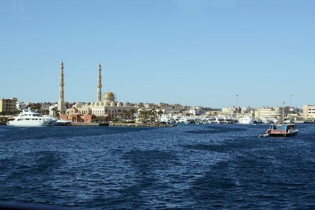Vista sul mare di hurghada con moschea centrale musulmana e porto di yacht e barche moderni
