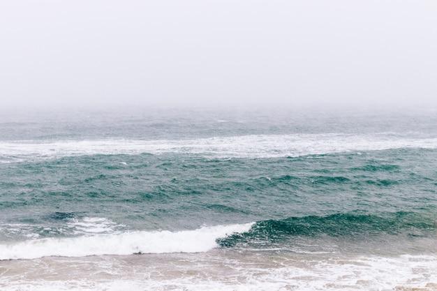Vista sul mare di inverno minimalista in tempo nevoso
