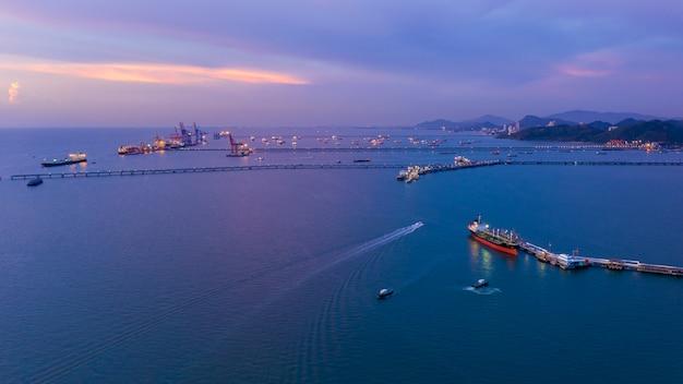 Vista sul mare di twilight e porto di spedizione che caricano petrolio e gas sul mare