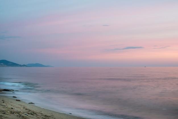 Vista sul mare mediterranea al tramonto con le montagne.