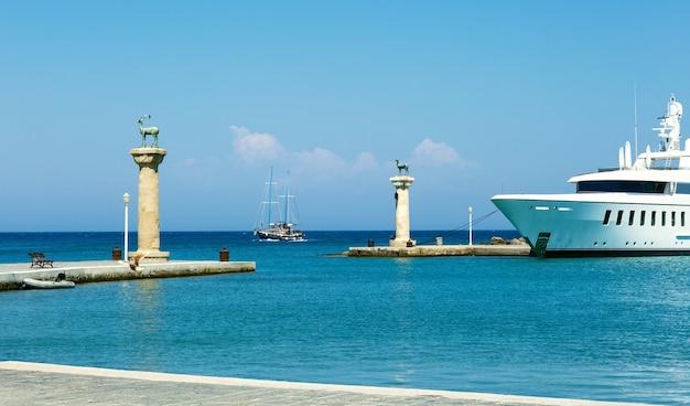 Vista sul mare su statue di cervi e navi all'entrata del porto di mandraki, dove sorgeva il colosso di rodi, in grecia